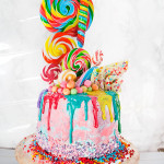 Rainbow Lollipop Birthday Cake - Dark Chocolate Mud Cake with Coffee Liquor, filled with boozy Raspberry sauce and Vanilla Swiss Meringue Buttercream. Covered with Pink and Blue Vanilla Swiss Meringue Buttercream and Dripping Rainbow White Chocolate Ganache. Decorated with Rainbow Lollipops! The most fun you can have with a birthday cake!