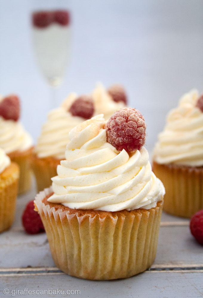 Orange and Raspberry Cupcakes with Prosecco Buttercream Frosting - fluffy, moist zesty orange cakes with raspberries baked into the centre, topped with creamy, fluffy prosecco buttercream frosting! The perfect cupcake for any celebration!