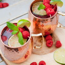 Raspberry Moscow Mule - High quality vodka combined with spicy and bubbly ginger ale, fresh lime juice and sweet, tart raspberries in a cold copper mug. This Raspberry Moscow Mule is a summery twist on the classic cocktail.