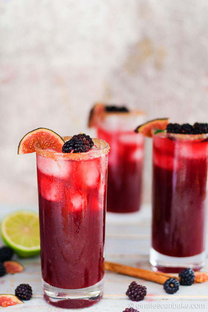 Blackberry, Cinnamon and Fig Margarita - one margarita in a tall glass in focus, with two drinks in background