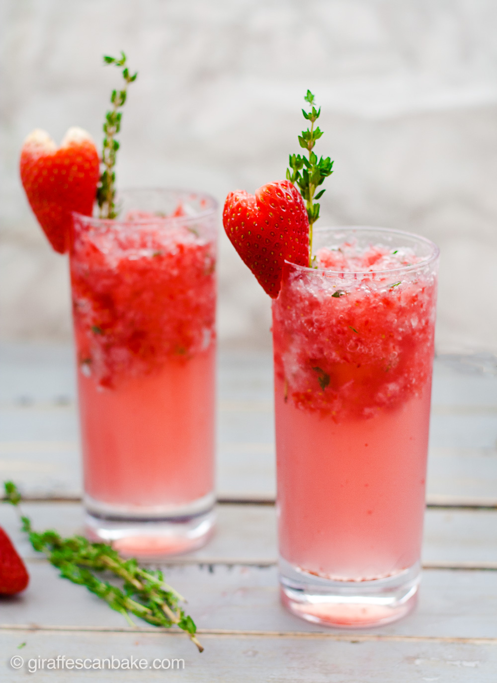 Strawberry & Thyme Slushie Cocktails - These Strawberry and Thyme Slushie Cocktails are not only gorgeous, they're totally delicious too. Sweet strawberries are muddled with aromatic thyme and white rum, add some crushed strawberry ice and soda water and you have the perfect Valentine's Day cocktail to share with your sweetheart.