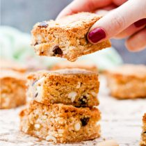 Gluten Free Triple Peanut Blondies - Chewy, moist and packed full of delicious peanut goodness. A peanut butter lover's dream come true! - Taking a blondie from the stack