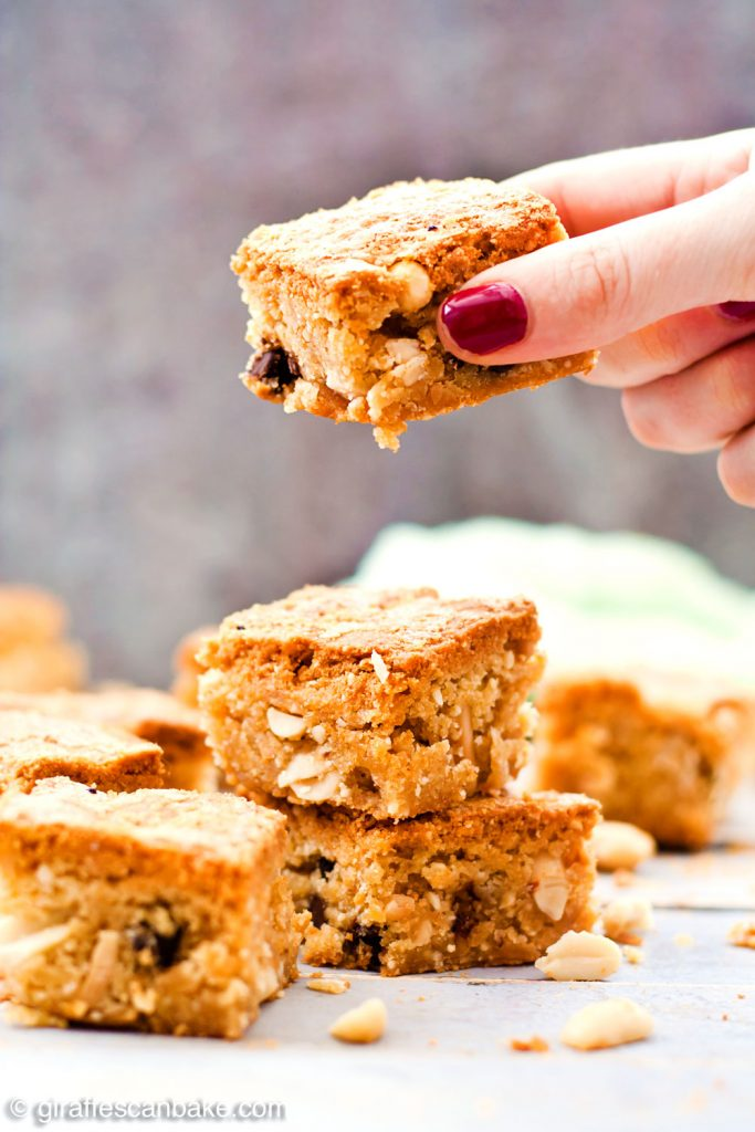 Gluten Free Triple Peanut Blondies - Chewy, moist and packed full of delicious peanut goodness. A peanut butter lover's dream come true! - Taking a blondie from the pile