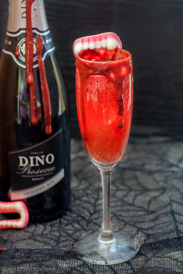 The Bloody Bellini, delicious blood is combined with bubbly prosecco to make the perfect Halloween Cocktail for Vampires, and those suffering with anaemia. If you're not a vampire, you can make this gruesome looking cocktail with Raspberry Puree and Raspberry Chocolate Syrup! Perfect to serve this halloween, and totally delicious too! #halloween #cocktail #bellini