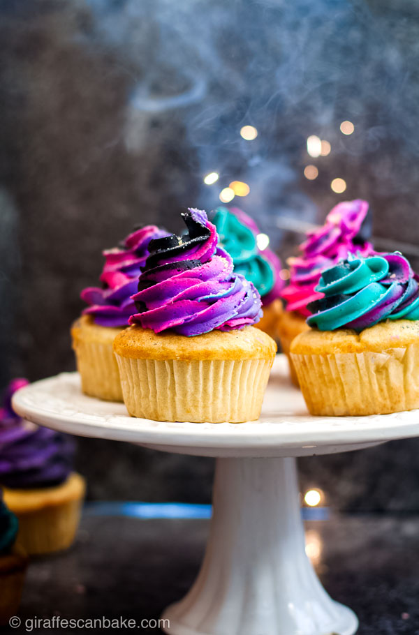 Fireworks Cupcakes - Four gluten free vanilla cupcakes with black buttercream swirled with neon buttercream on a white cake stand with sparks from a sparkler in the background
