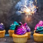 Fireworks Cupcakes - gluten free vanilla cupcakes with black buttercream swirled with neon buttercream, and a sparkler above them - square cropped image
