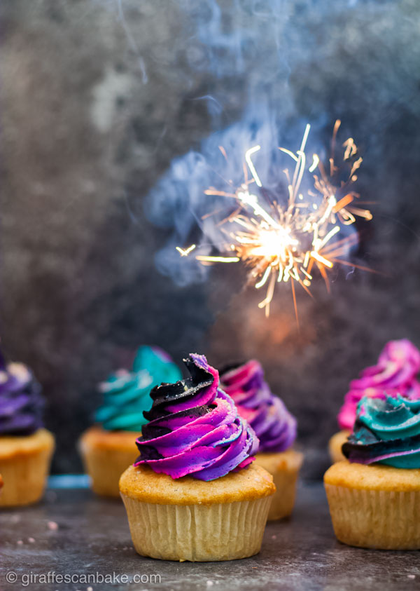 Fireworks Cupcakes - Gluten free vanilla cupcakes with black buttercream swirled with neon buttercream, there is a sparkler above them - full size image