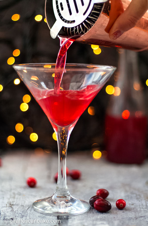 The Cranberry Martini is a sweet and slightly tart festive cocktail, made with a homemade cranberry shrub to give it a little bit of zing - the cranberry martini being poured into a martini glass