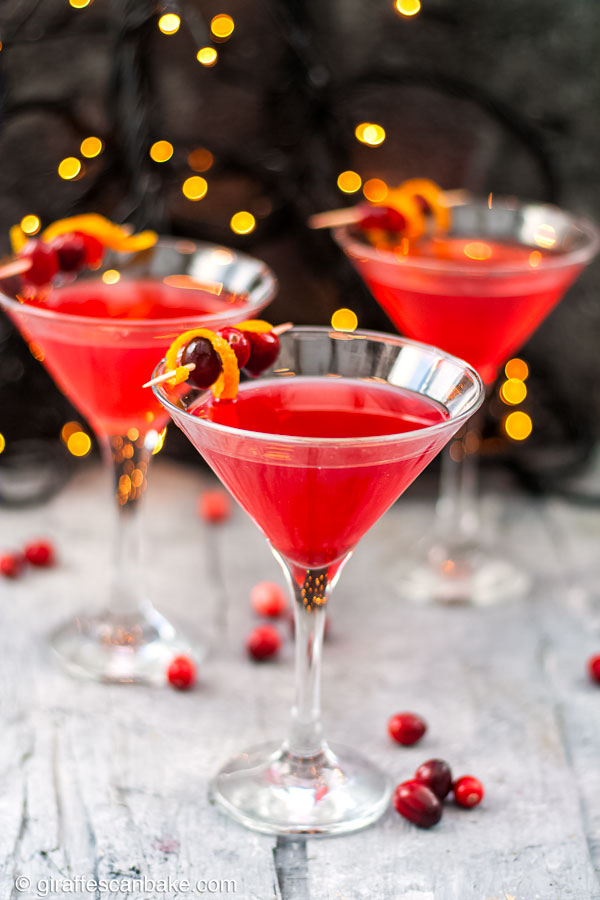 The Cranberry Martini is a sweet and slightly tart festive cocktail, made with a homemade cranberry shrub to give it a little bit of zing - a cranberry martini with two in the background