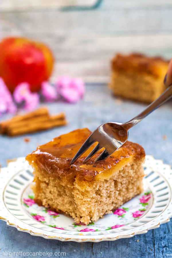 A fork digging into the top of a piece of Gluten Free Apple Upside Down Cake on a white and pink plate