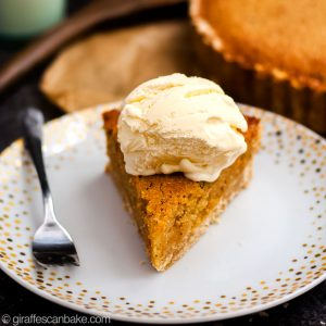 Gluten Free Treacle Tart - a slice of treacle tart with ice cream on top, square cropped image