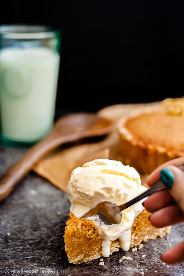 Gluten Free Treacle Tart - a slice of treacle tart with ice cream on top, and a fork digging in