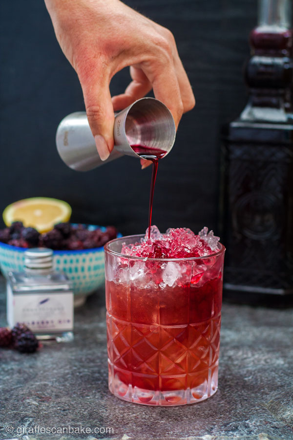 The Mulberry Bramble Cocktail - blackberry liqueur being poured on top of the cocktail