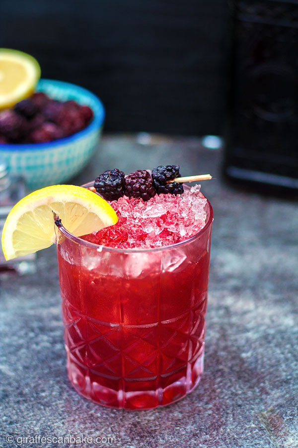 The Mulberry Bramble Cocktail - photo of finished cocktail with a lemon wedge and blackberries as a garnish