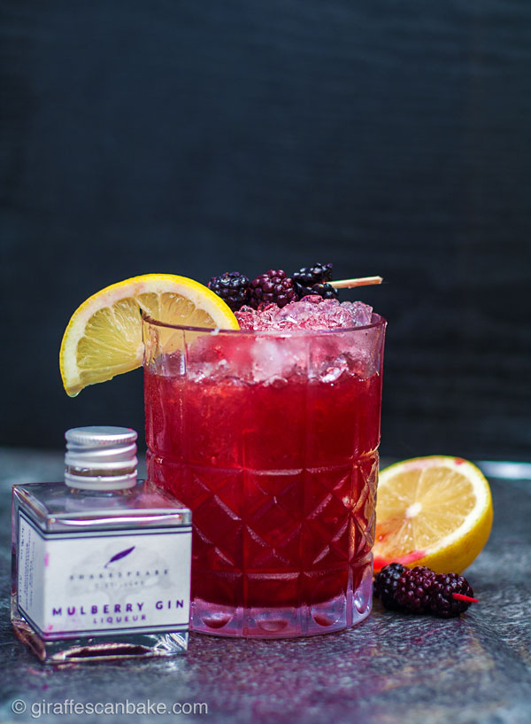 The Mulberry Bramble Cocktail - a photo of the finished cocktail at a front on angle, with a small bottle of mulberry gin next to it