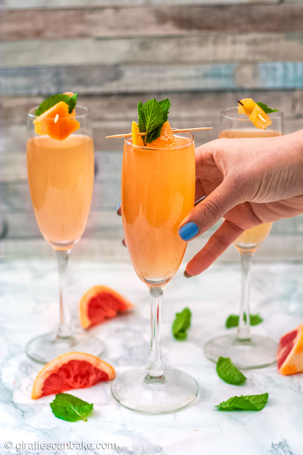 Brandy Grapefruit Mimosa - three mimosas, one being picked up