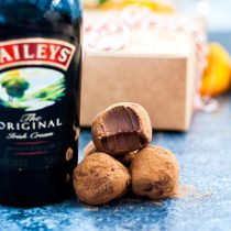Chocolate Orange Baileys Truffles are a decadent chocolate treat everybody is going to love. Made with festive chocolate orange and rich, creamy Bailey's! - three truffles next to a bottle of baileys, one has a bite taken out of it. square cropped photo