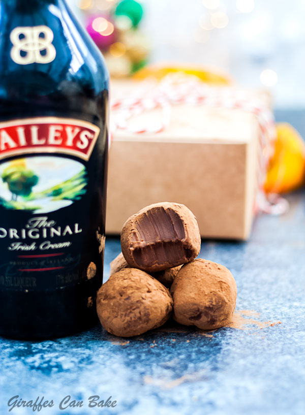 Chocolate Orange Baileys Truffles are a decadent chocolate treat everybody is going to love. Made with festive chocolate orange and rich, creamy Bailey's! - three truffles next to a bottle of baileys, one has a bite taken out of it