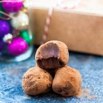 Chocolate Orange Baileys Truffles are a decadent chocolate treat everybody is going to love. Made with festive chocolate orange and rich, creamy Bailey's! - three truffles, one has a bite taken out of it, gift box in the background