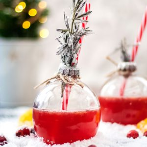 This Holiday Gin and Tonic is full of the festive flavours of cranberry and clementine - one bauble glass in focus, with red gin and tonic and rosemary, square cropped