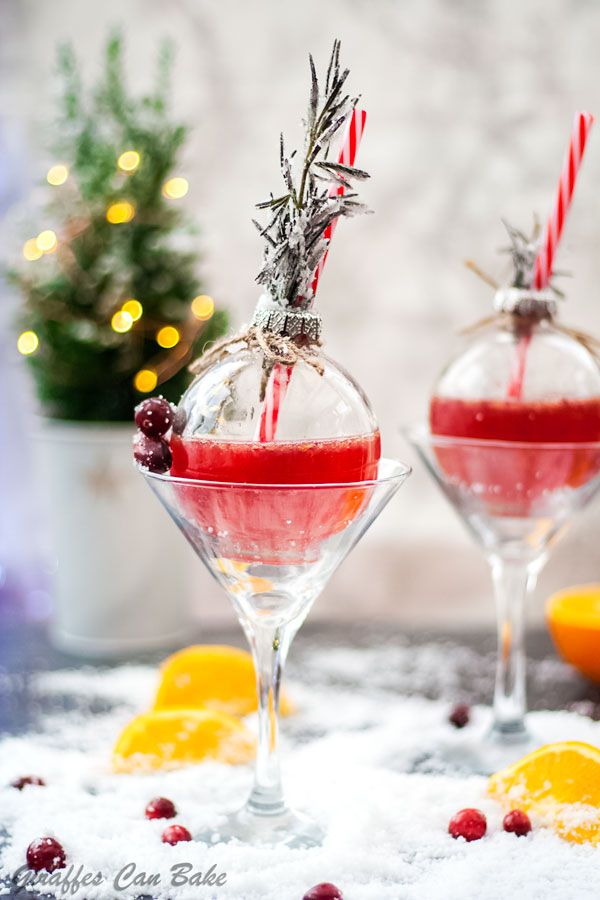 This Holiday Gin and Tonic is full of the festive flavours of cranberry and clementine - two bauble glasses with red gin and tonic, in martini glasses