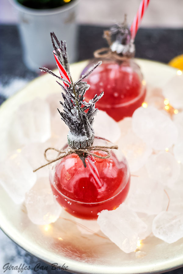 This Holiday Gin and Tonic is full of the festive flavours of cranberry and clementine - two bauble glasses with red gin and tonic in a bowl of ice
