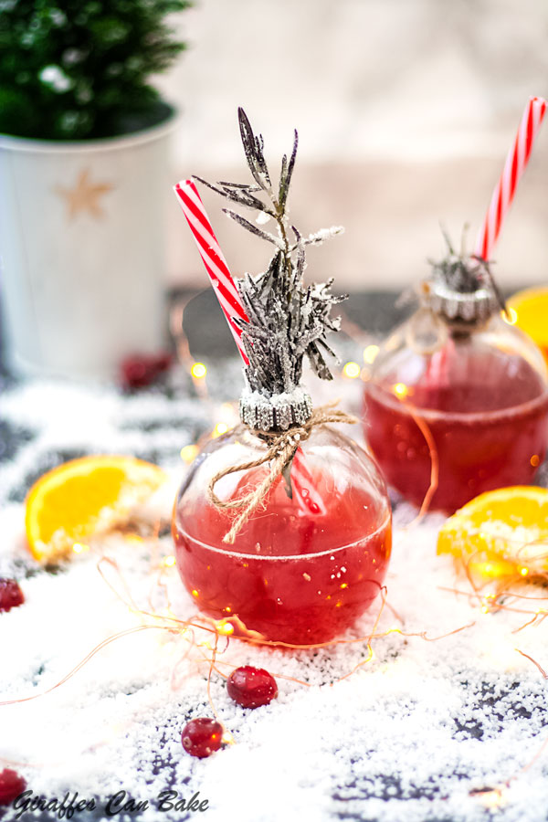 This Holiday Gin and Tonic is full of the festive flavours of cranberry and clementine - bauble glasses with red gin and tonic, sprigs of rosemary in top