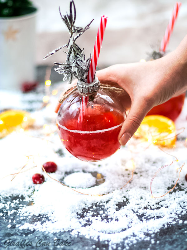 This Holiday Gin and Tonic is full of the festive flavours of cranberry and clementine - bauble glass with red gin and tonic, held in a hand