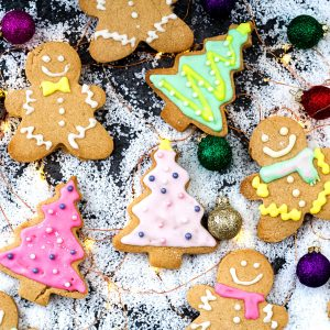 These buttery, melt in your mouth Gluten Free Shortbread Cookies with Cinnamon & Clementine are the perfect Christmas cookies - Christmas tree and gingerbread men shaped cookies on snow with christmas baubles, square cropped