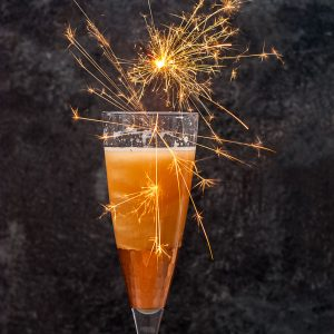Shimmery New Years Eve Cocktail - champagne glass filled with gold shimmery cocktail, with lots of sparklers over the top, square cropped image