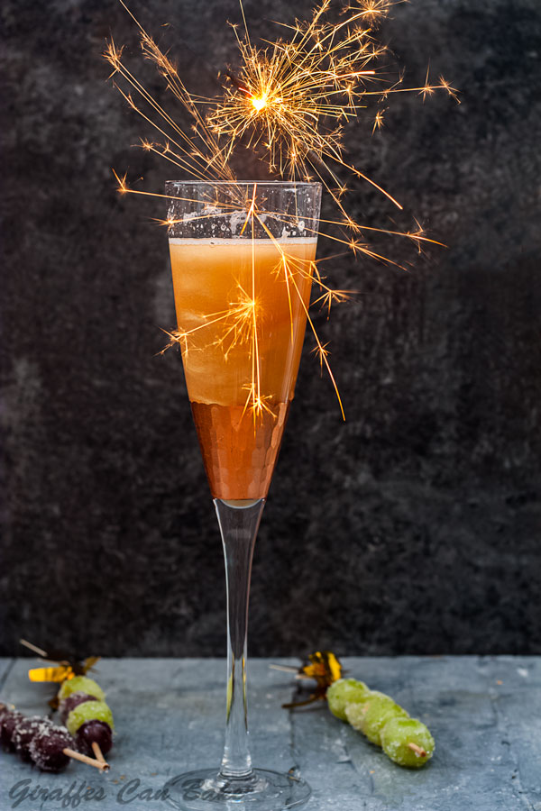 Shimmery New Years Eve Cocktail- a tall champagne glass with gold shimmery cocktail, lots of sparklers over the top