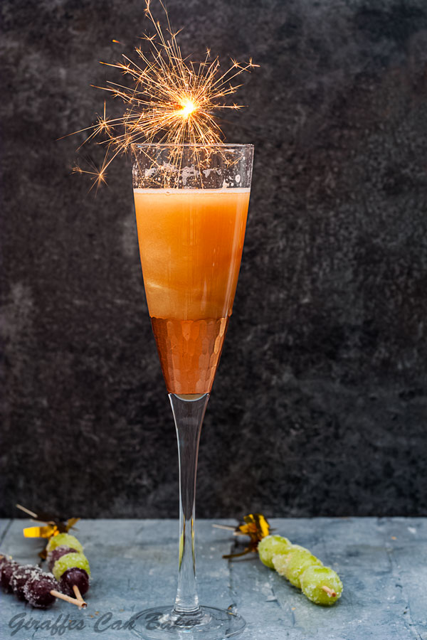 Shimmery New Years Eve Cocktail - champagne glass filled with gold shimmery cocktail, a small sparkler over the top