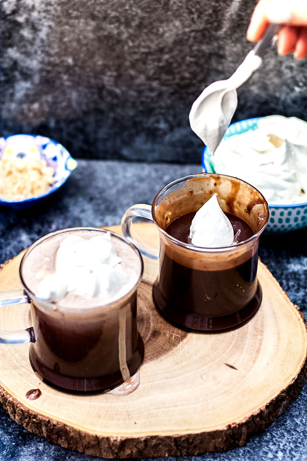 Hazelnut Italian Hot Chocolate - whipped cream being spooned into mug of hot chocolate