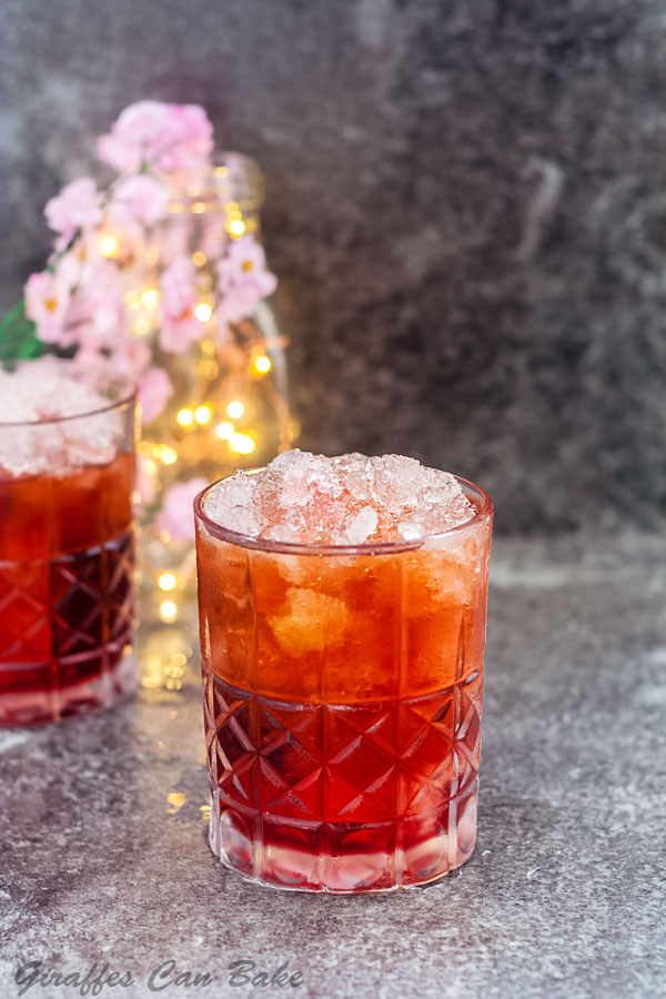 A Valentine's Day cocktail on a rocks glass in front, another in background with pink flowers and fairy lights