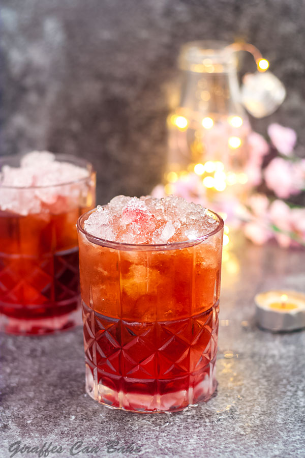 A red Valentine's Day cocktail in front, one is behind, there are pink flowers and lights in the background to the right