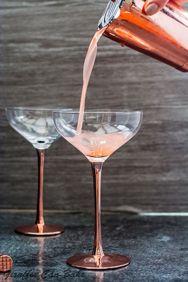 The Cupid's Cup - a Pisco Sour Variation - the cocktail is being poured into a coupe cocktail glass, empty glass in the background
