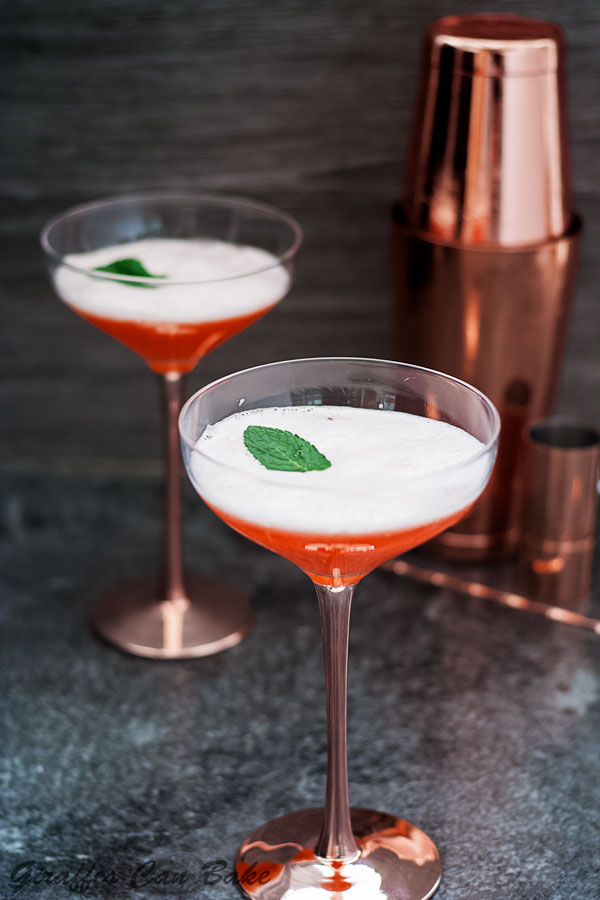 The Cupid's Cup - a Pisco Sour Variation - orange coloured cocktails in two coupe glasses