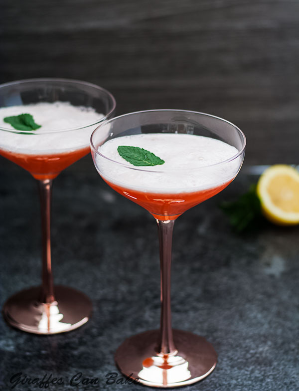 The Cupid's Cup - a Pisco Sour Variation - two coupe cocktail glasses next to each other, with orange cocktail and mint leaf
