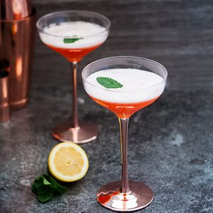 The Cupid's Cup - a Pisco Sour Variation - two orange coloured cocktails in coupe glasses, white foam on top. square cropped