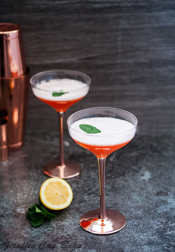 The Cupid's Cup - a Pisco Sour Variation - two orange coloured cocktails in coupe glasses, white foam on top