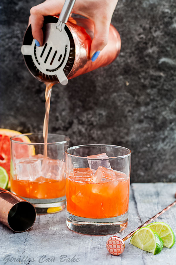 The Campanella - a Paloma Cocktail Variation - an old fashioned glass filled with an orange cocktail, more cocktail is being poured into a glass in the background from a copper shaker