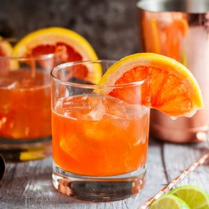The Campanella - a Paloma Cocktail Variation - old fashioned glass of orange cocktail, another in the background, garnished with half a grapefruit wheel - square cropped image