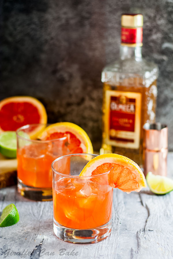The Campanella - a Paloma Cocktail Variation - two old fashioned glasses filled with orange cocktail, bottle of tequila is in the background on the right, a cut grapefruit and lime is in the background on the left