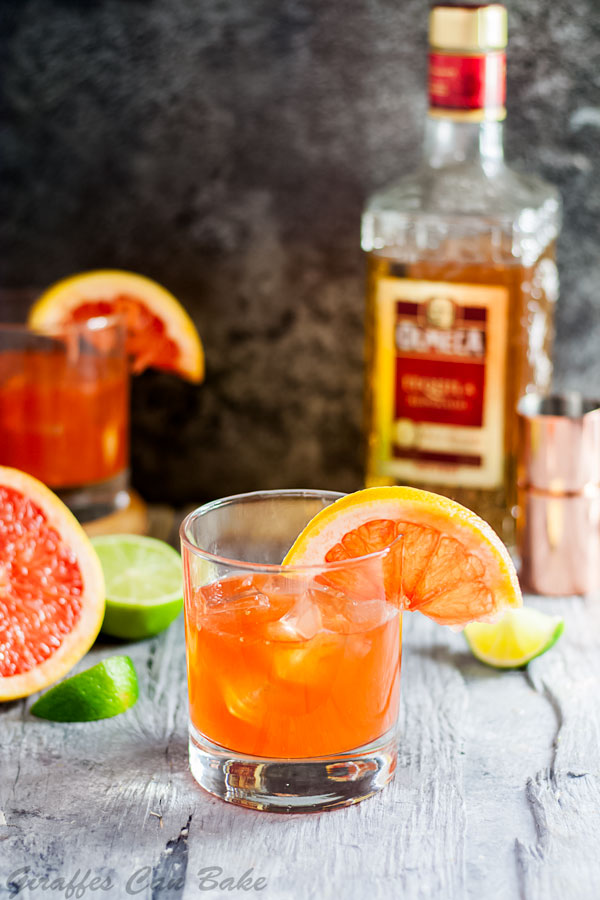The Campanella - a Paloma Cocktail Variation - one old fashioned glass with orange cocktail, half a grapefruit wheel garnishes the glass. Another cocktail sits in the background on the left, a bottle of tequila is on the right in the back
