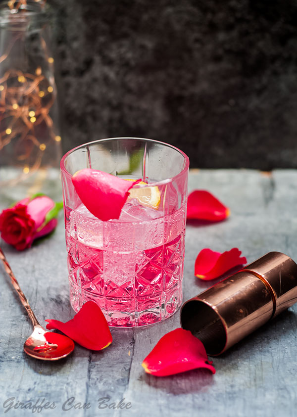 Rose Vodka Tonic Mixed Drink Cocktail - rocks glass with a pink liquid, rose petals surround with a jigger and stirring spoon
