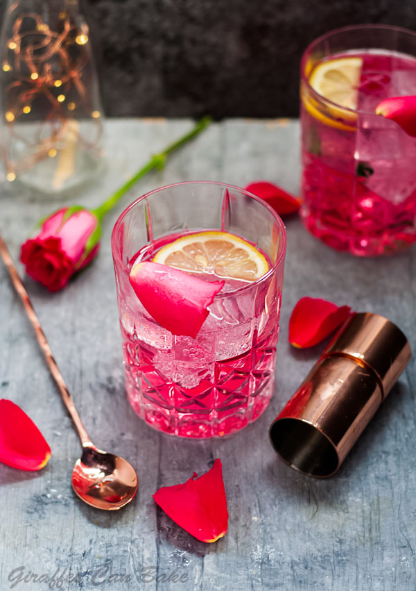 Rose Vodka Tonic Mixed Drink Cocktail - above view of cocktail in rocks glass with rose, jigger and stirrer surrounding