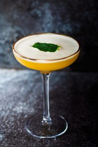 a coupe cocktail glass with mocktail, yellow liquid and green mint leaf